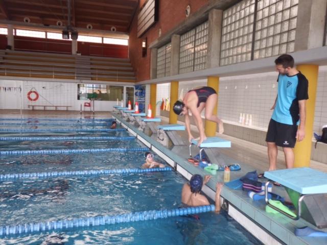 Una alumna lanzándose a la piscina del pabellón deportivo