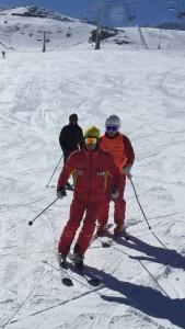 Primer plano de monitor y alumno esquiando