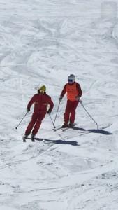 Monitor y alumno descendiendo por la nieve
